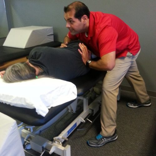 Amit leaning in to apply traction to the lumbosacral joint to improve spine mobility and decrease pain.